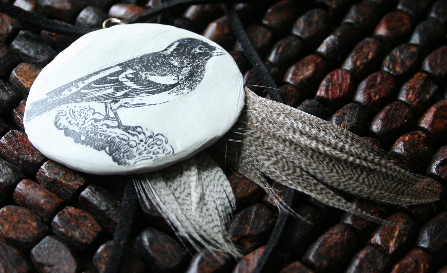 bird oval with feathers black cord close